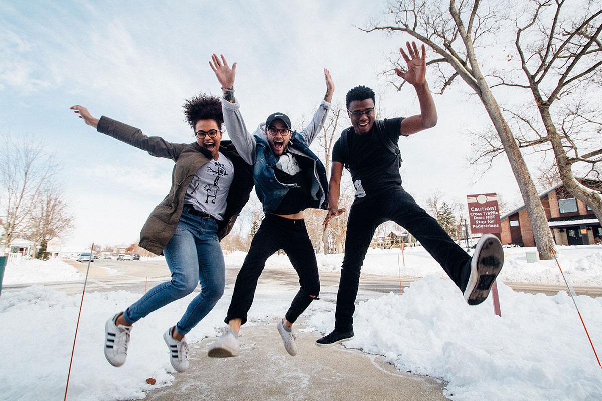 Three smiling young adults mid-jump on a snowy sidewalk