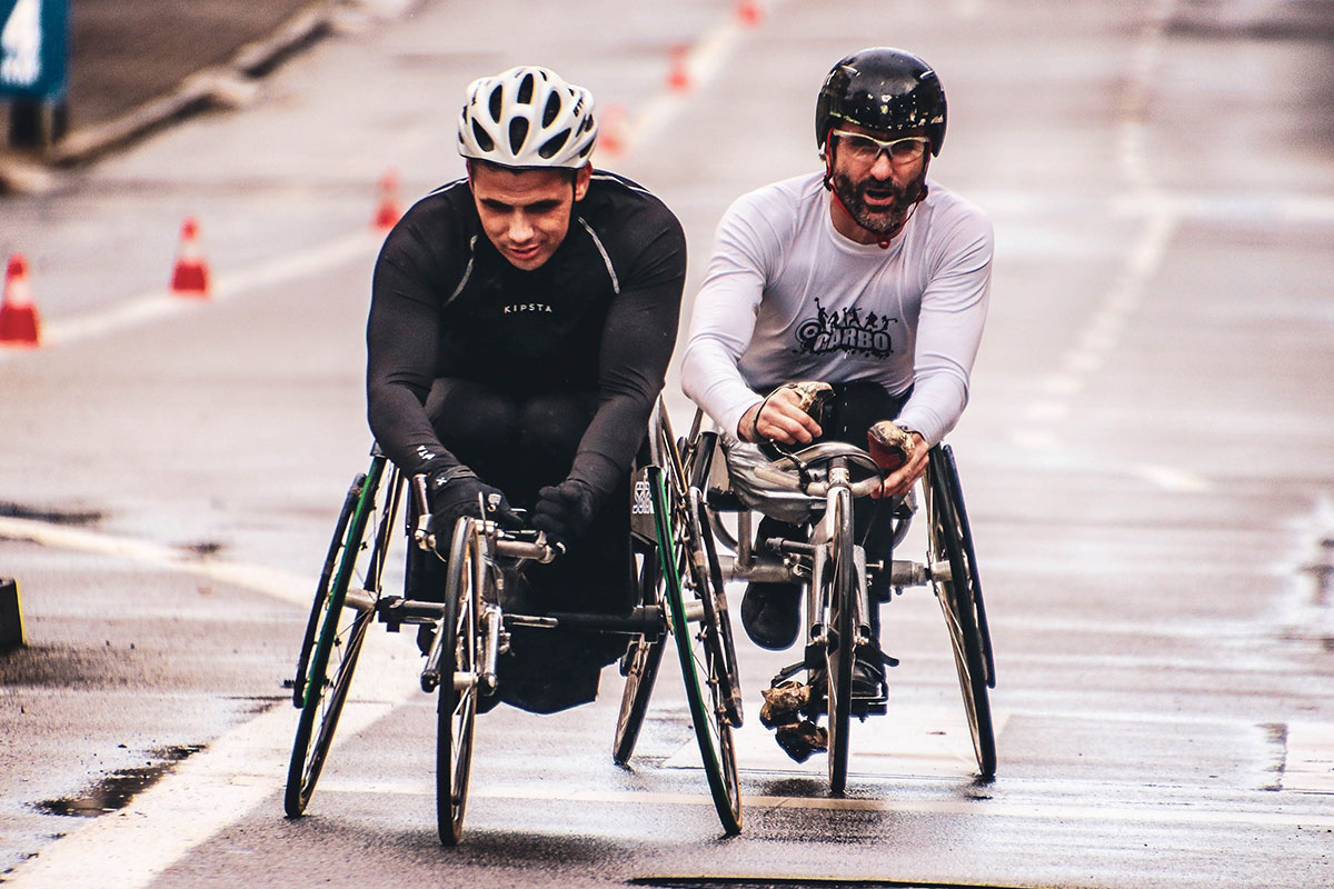 Two young adults with helmets wheelchair racing