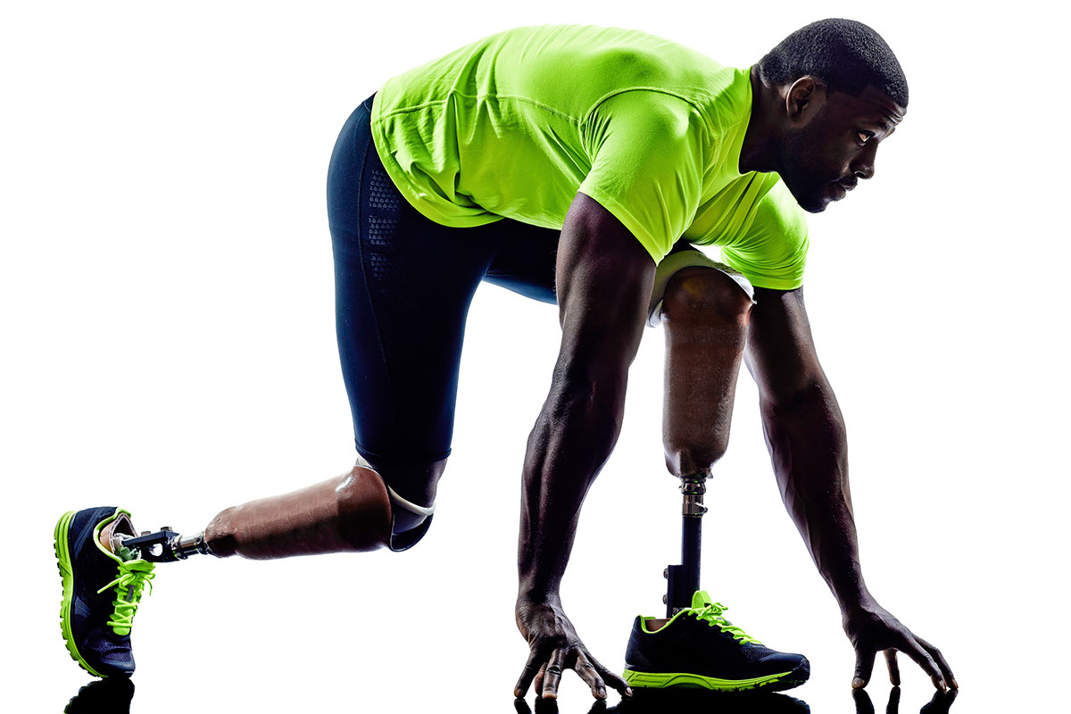 African-American man with prosthetic leg wearing running attire and crouching in starting position