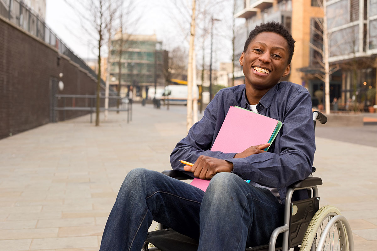 An African-American young adult male in a wheelchair smiling and holding school supplies