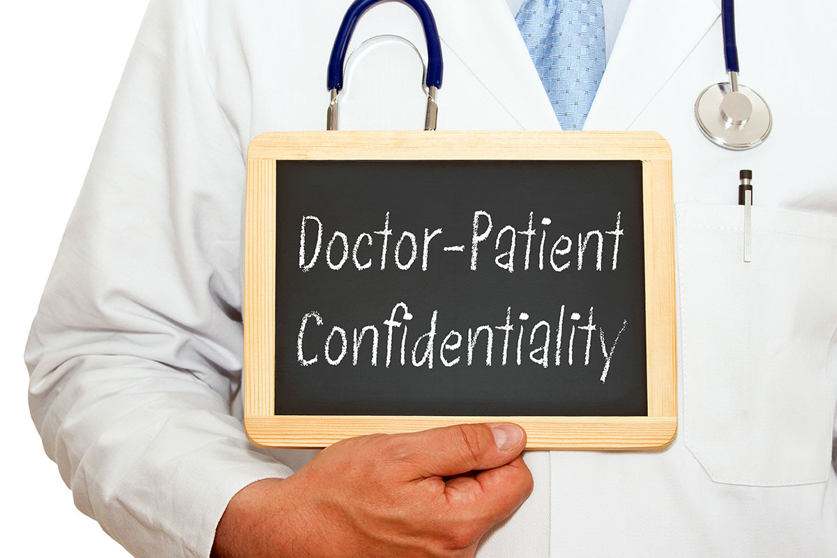 Doctor holding up small chalkboard that reads Doctor Patient Confidentiality