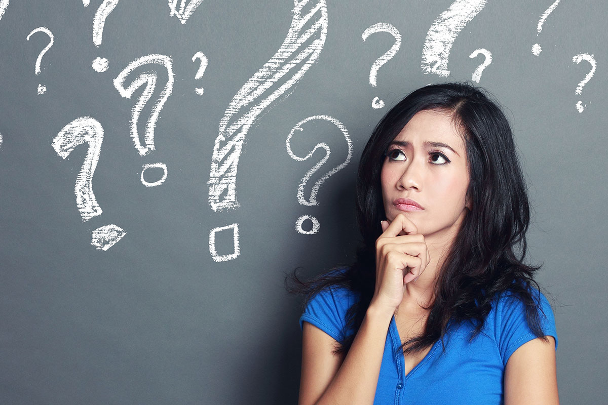 Puzzled Asian female with question marks above her head