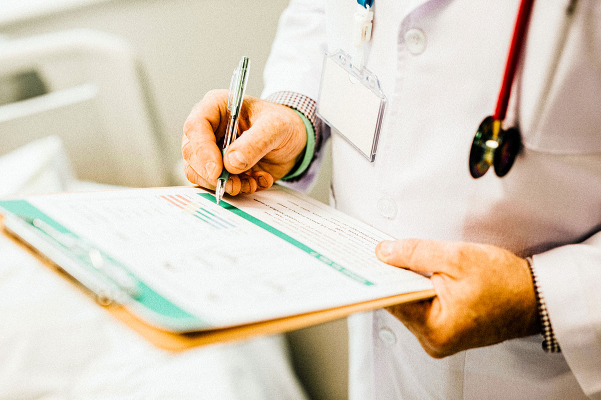 The hands of a white doctor writing on paper on a clipboard