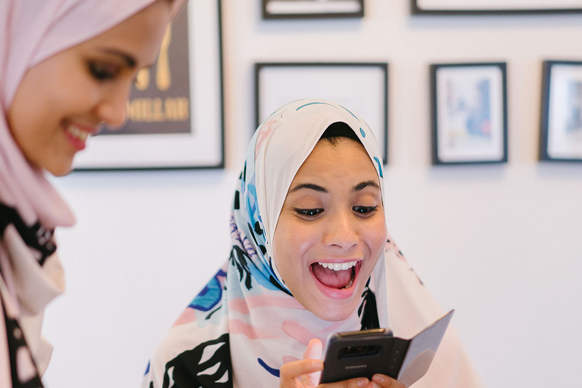 2 smiling young women in white and pink hijabs eating food and playing on smartphone