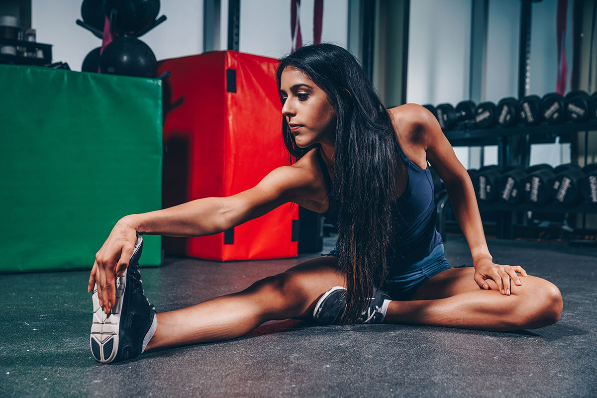 Indian young adult female wearing workout clothes in a gym stretching on the floor