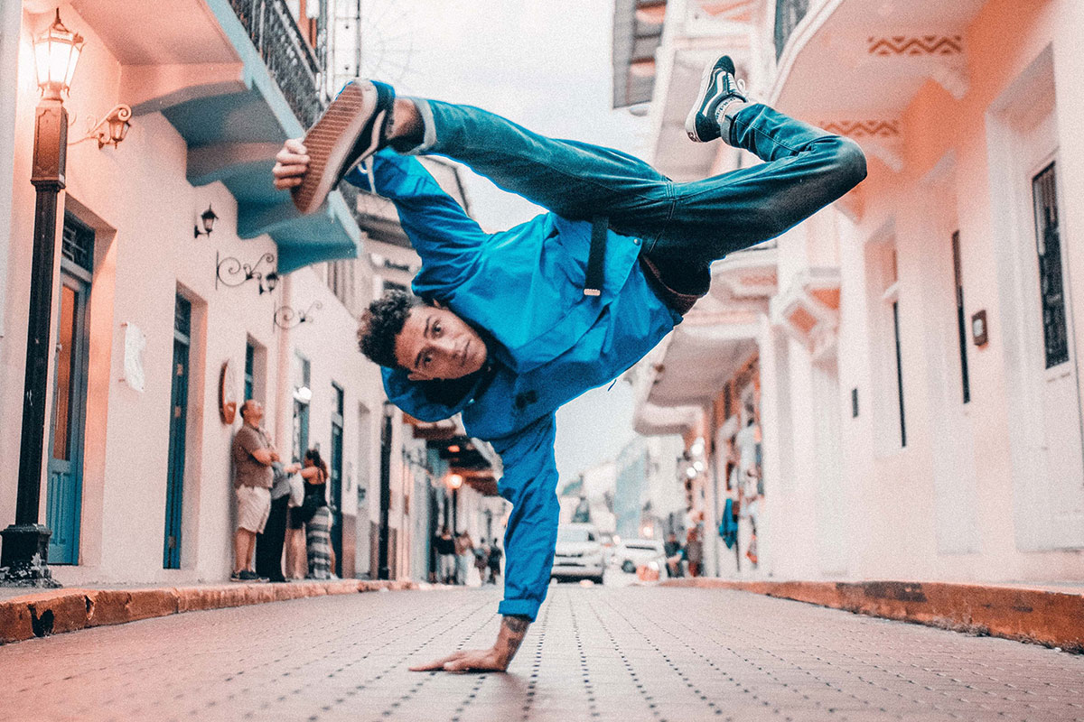 Hispanic young adult man breakdancing in street