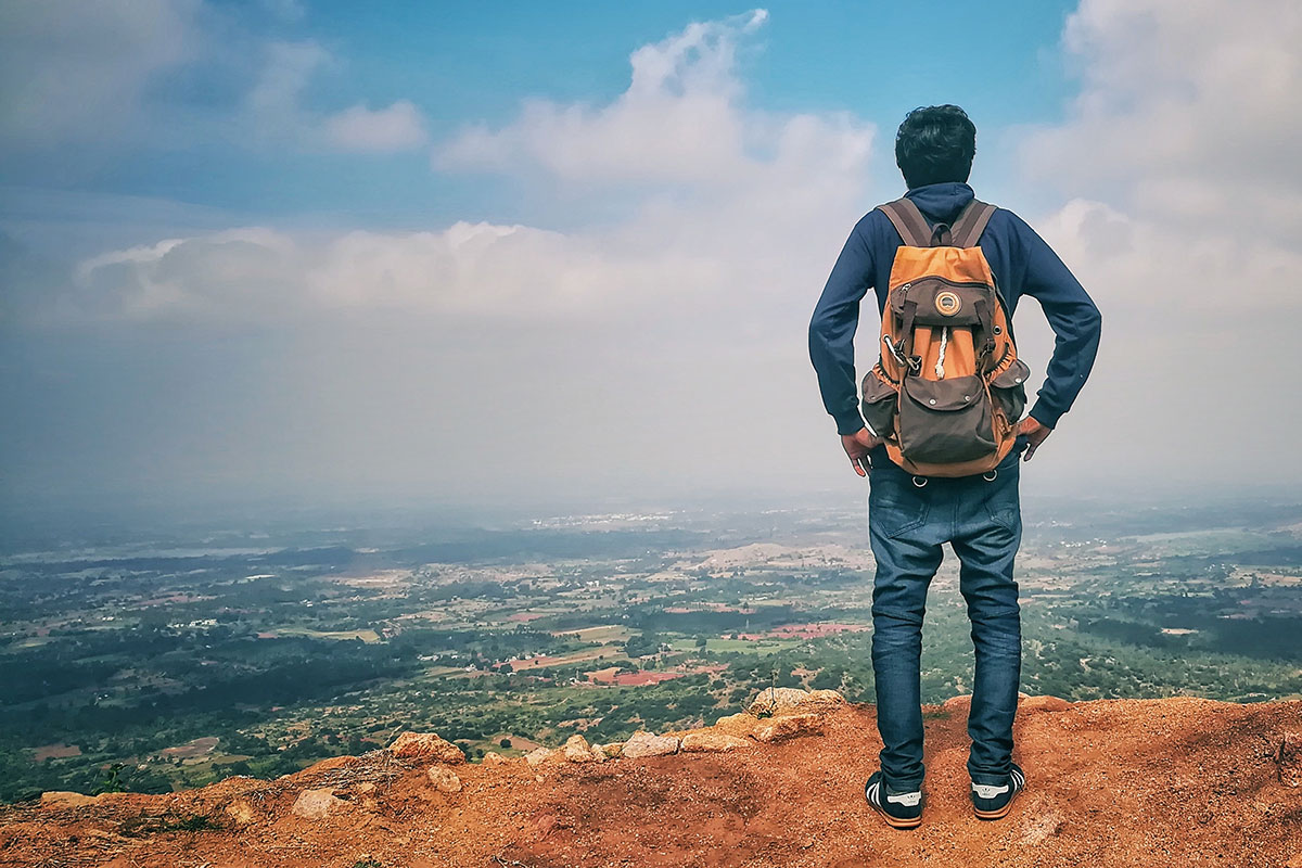 Young adult man in blue jeans with backpack looking at horizon